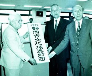財団設立の日に看板を掲げる当時の理事長ほか